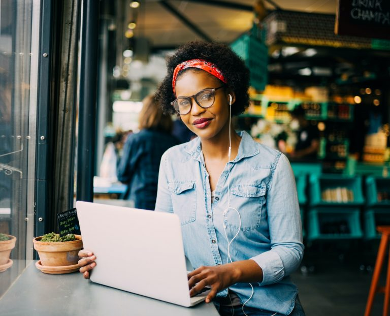 Confident young African woman working online in a cafe