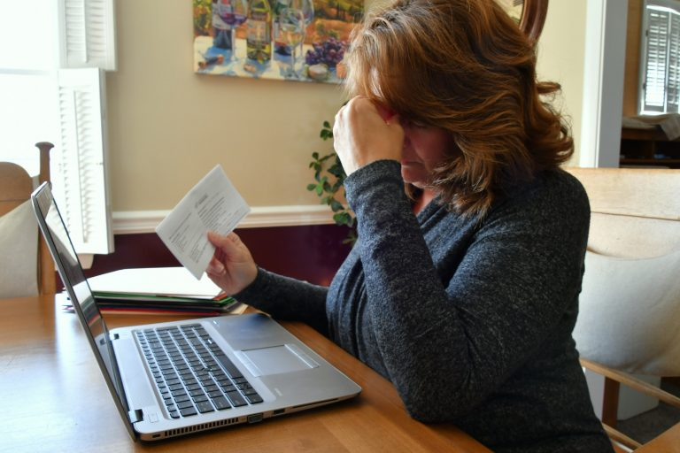 Female using laptop with her head in her hands trying to cope with anxiety, worry, upset, stress