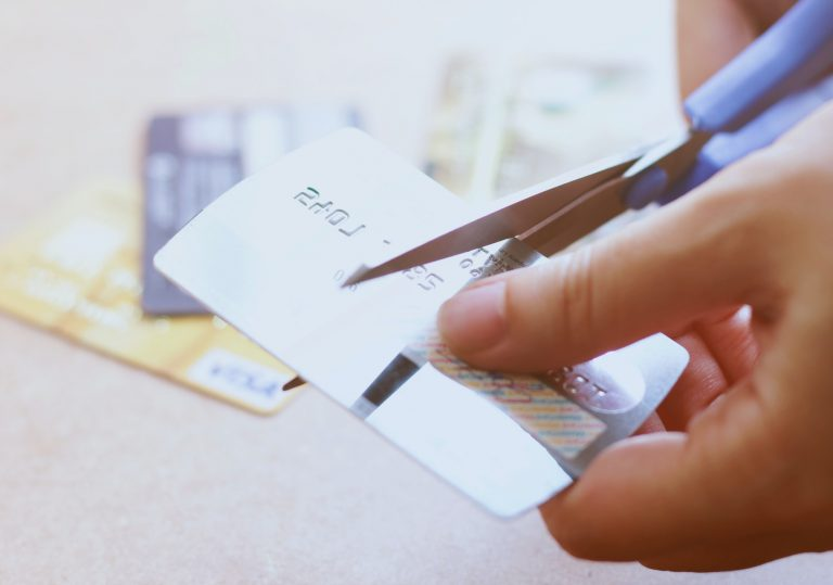 Hand cutting credit card with scissors