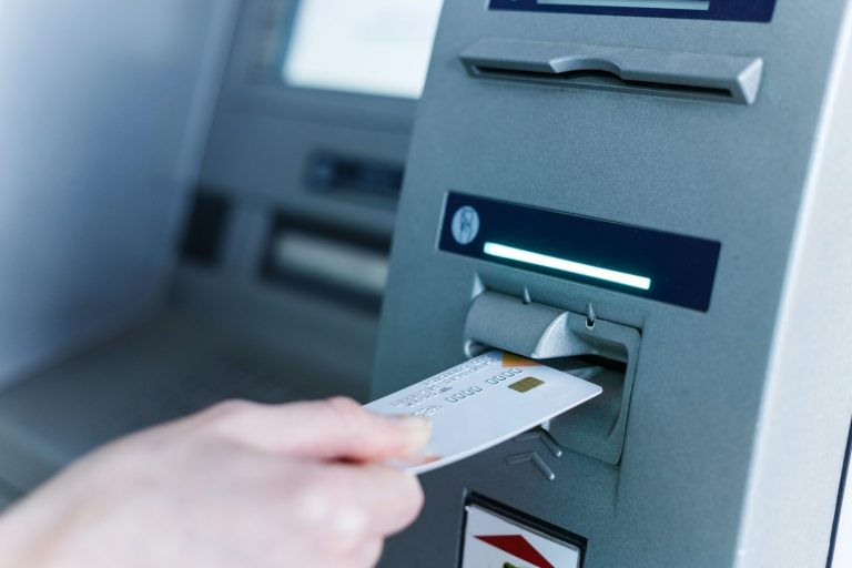 Person insert card to automated teller machine. Cashing non-cash money by individual.