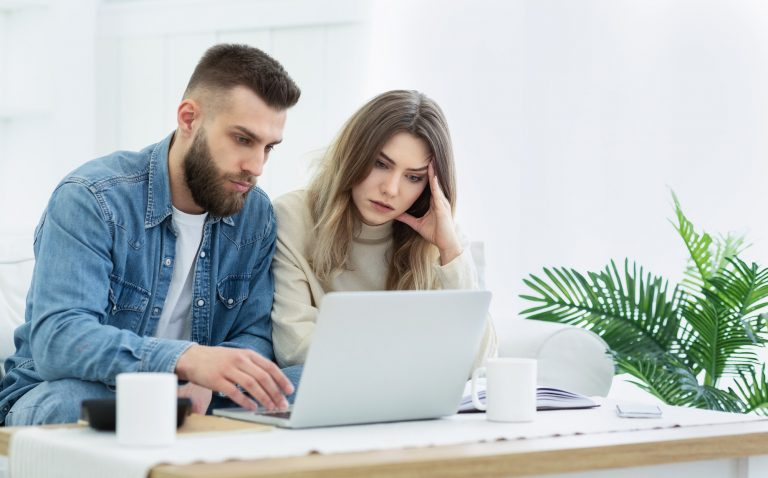 Young couple using laptop for managing expanses