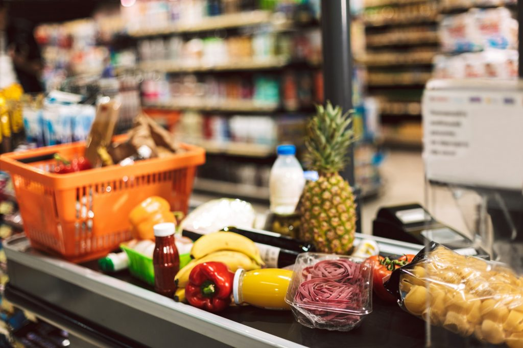 Close up shopping basket and fresh products on cashier desk in s