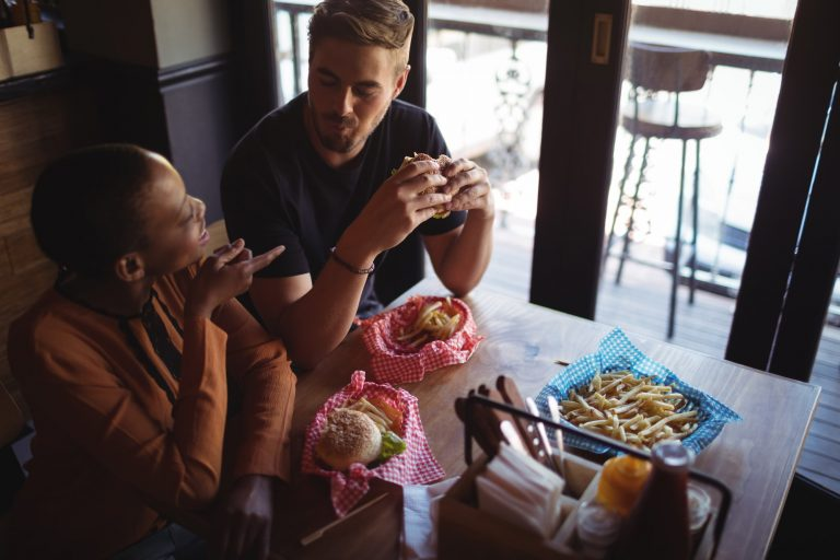 Happy couple interacting while having burger