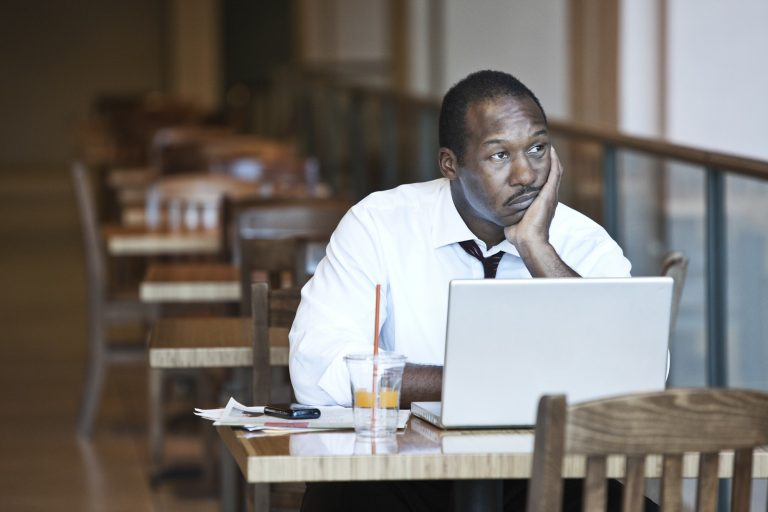 Black business man working on a lap top computer in a coffee shop.