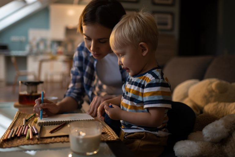 Content little boy painting with mother with colored pencils at home