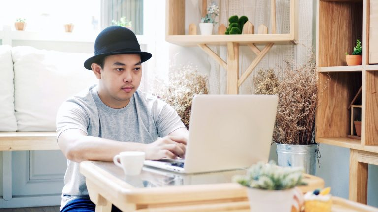 Asian freelance in casual suit sitting to work with technology laptop in modern co-working
