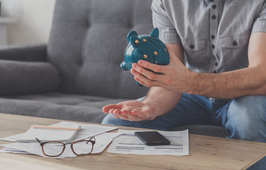Man sitting at a table full of unpaid bills shakes out the last penny from the piggy bank