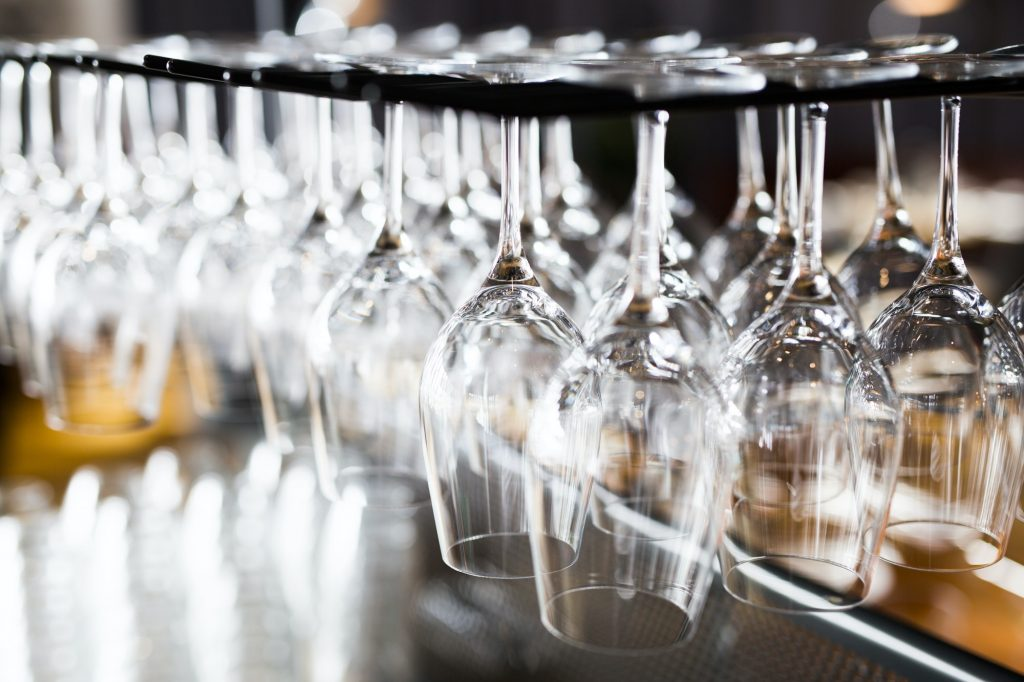 Wineglasses hanging from rack in bar